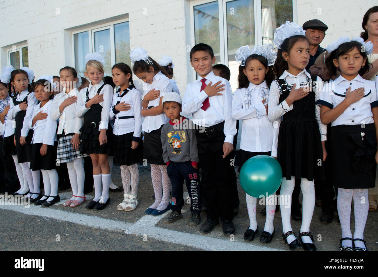 Students recite their national anthem during a 'first bell' celebration at Tort-kul school in Kyrgyzstan, - Stock Image