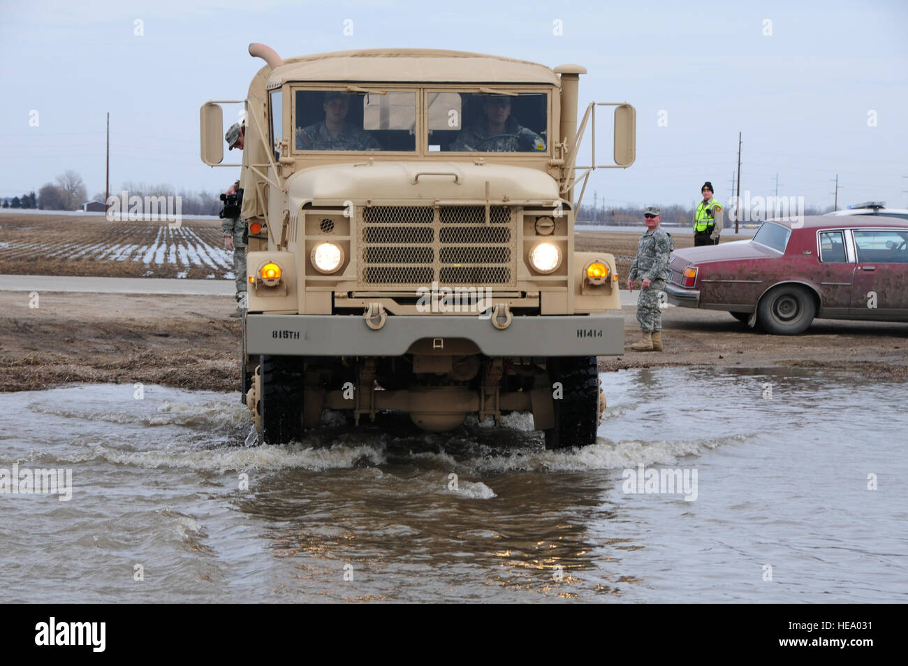 A North Dakota National Guard quick response force truck drives through over-land flood water that is covering a - Stock Image