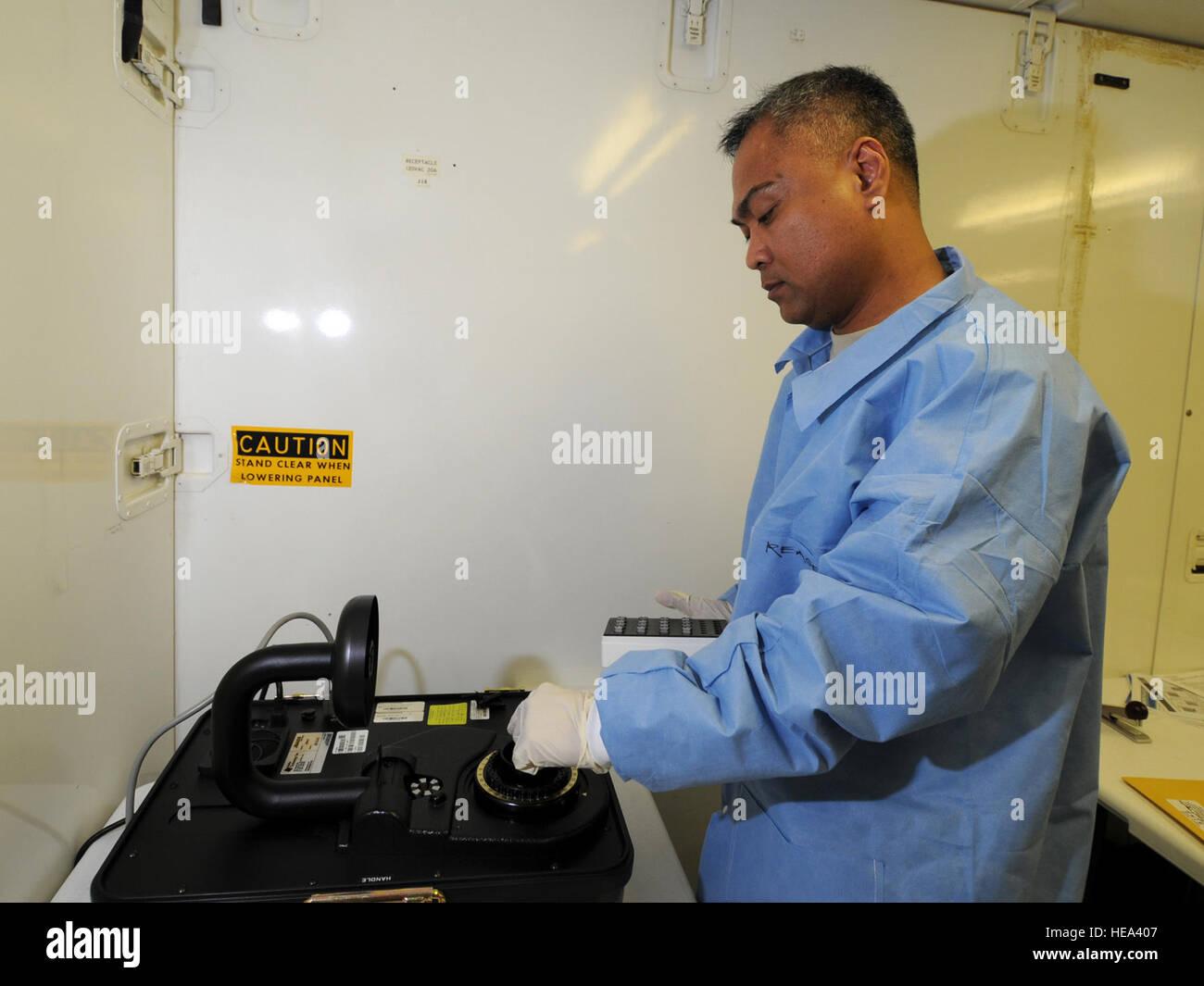 U.S. Air Force Maj. Lorenzo Gabiola, 379th Expeditionary Medical Group biological augmentation team chief, analyzes - Stock Image