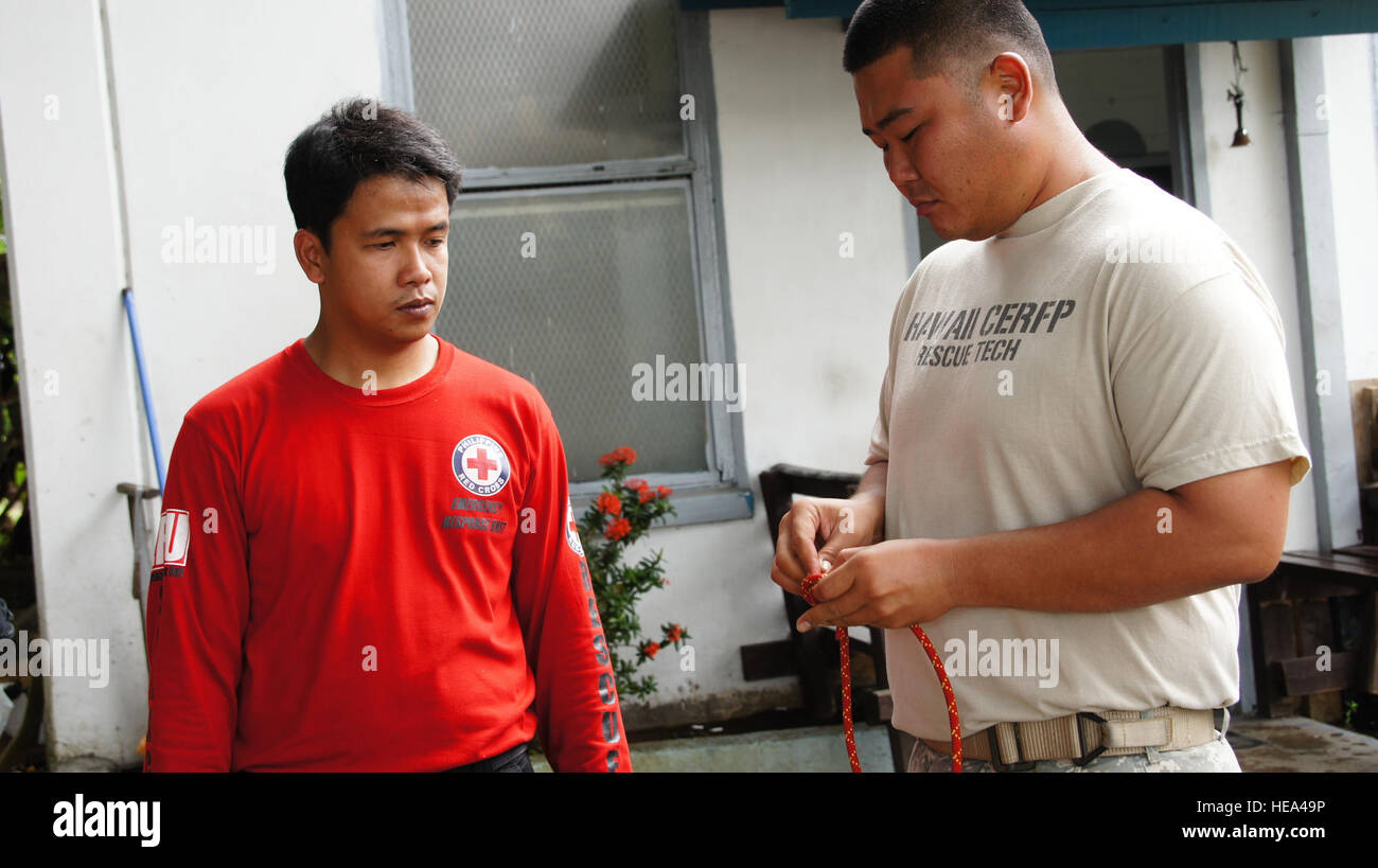 Staff Sgt. Cory Ito of the Hawaii Army National Guard, goes over basic rescue knot tying with a member of the Philippine - Stock Image