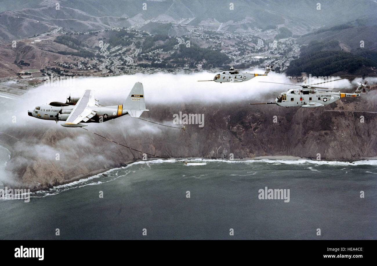 An air-to-air left side view of an HC-130 Hercules aircraft maneuvering to refuel two CH-3 Jolly Green Giant helicopters. - Stock Image