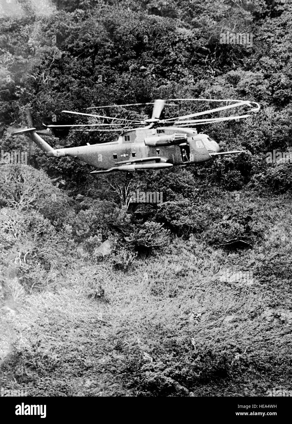 An HH-53C Super Jolly Green Giant helicopter hovers over the jungle during the rescue of a downed pilot.  (Substandard - Stock Image
