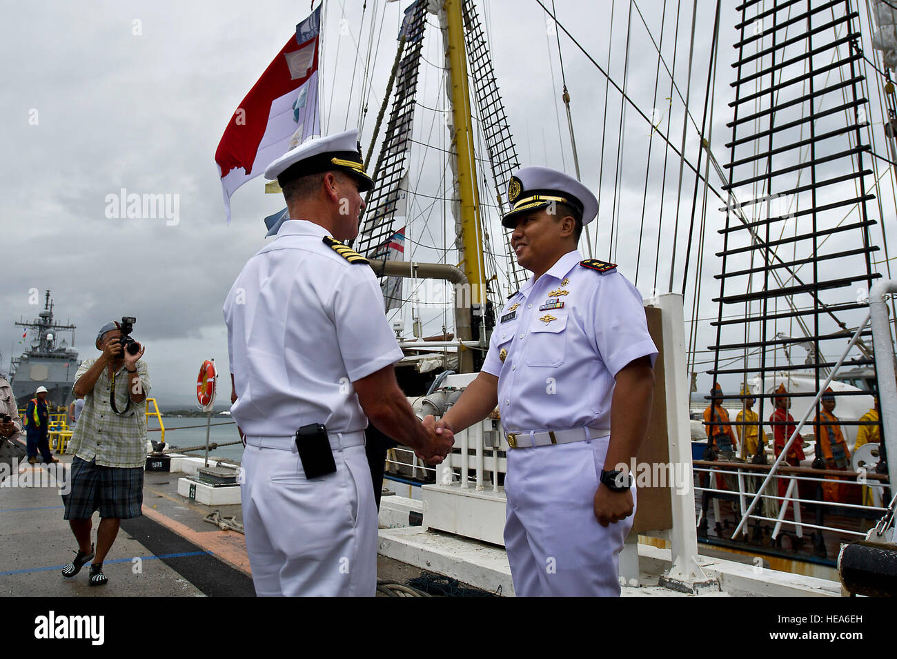 U.S. Navy Capt. Jeffrey James, from left, Joint Base Pearl Harbor-Hickam commander, greets Indonesian navy Cmdr. - Stock Image