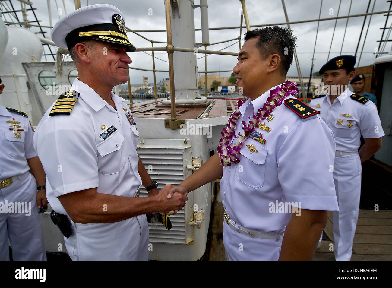 U.S. Navy Capt. Jeffrey James, from left, Joint Base Pearl Harbor-Hickam commander, gives a coin to Indonesian Navy - Stock Image