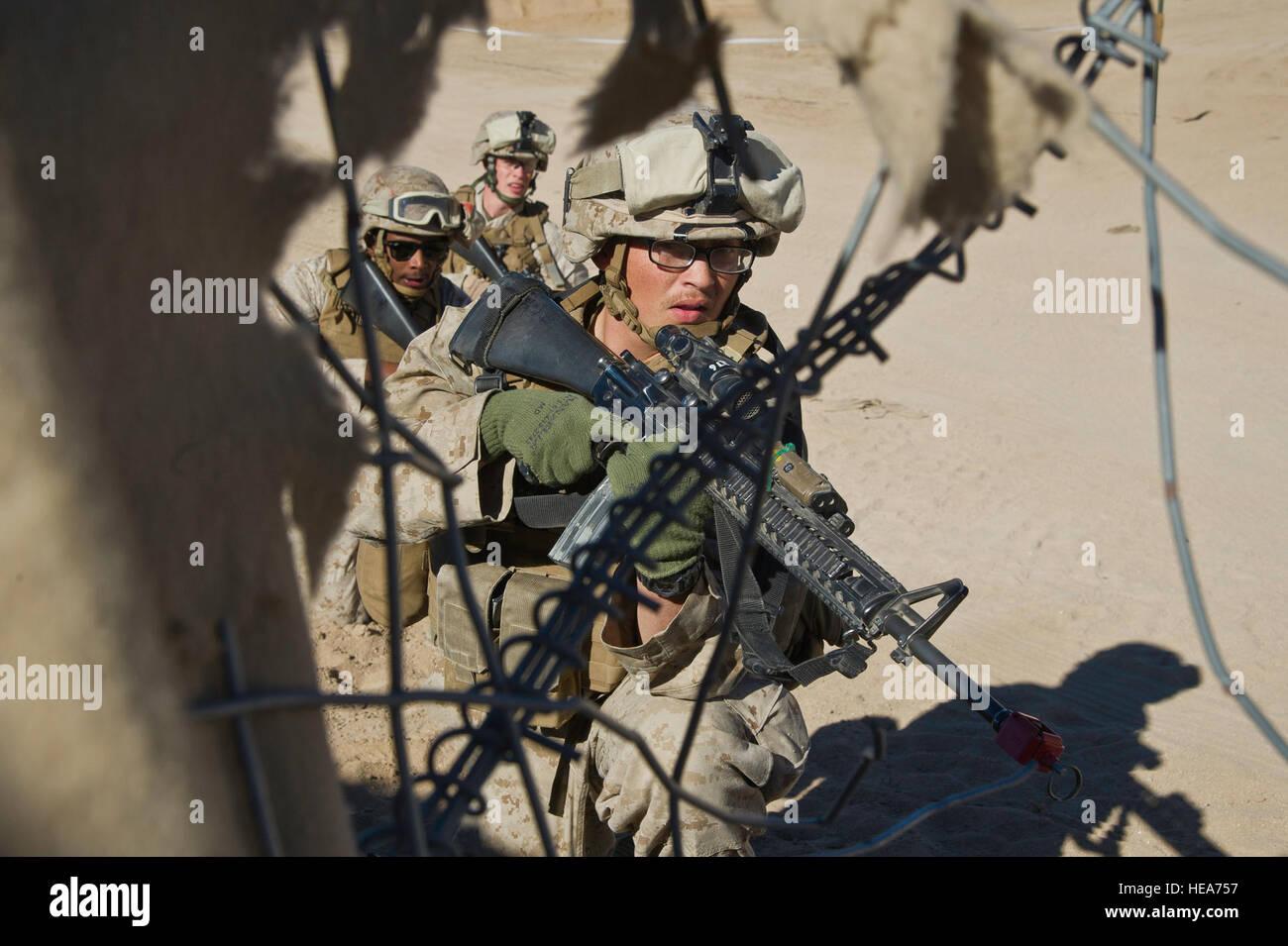 U.S. Marines assigned to 1st Marine Logistics Group, Marine Corps Base Camp Pendleton, Calif., take cover behind Stock Photo
