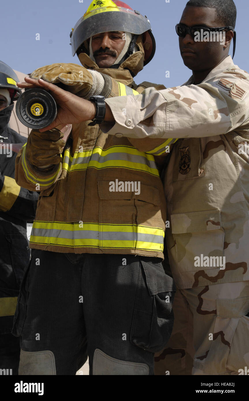 Staff Sgt. DeLon Branch instructs a local Iraqi firefighter on how to properly operate and aim a hose, Oct. 29. - Stock Image