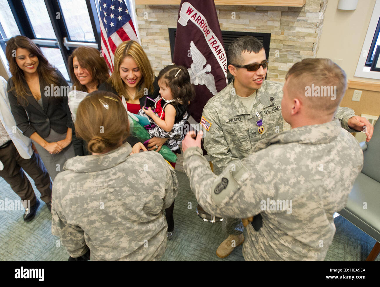 Army Sgt. Rigoberto Luviano, a native of Lexington, N.C., stands next to his family as he hugs a fellow soldier - Stock Image