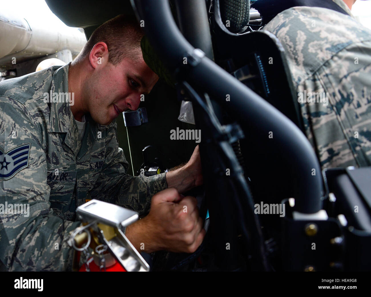 U.S. Air Force Staff Sgt. Samuel Taylor, 612th Air Base Squadron firefighter, tries to remove the pilot seat from Stock Photo