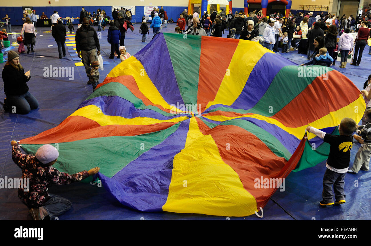 Children play with a parachute during the Family Fun and Fitness Fair inside the Buckner Gym on Joint Base Elmendorf - Stock Image