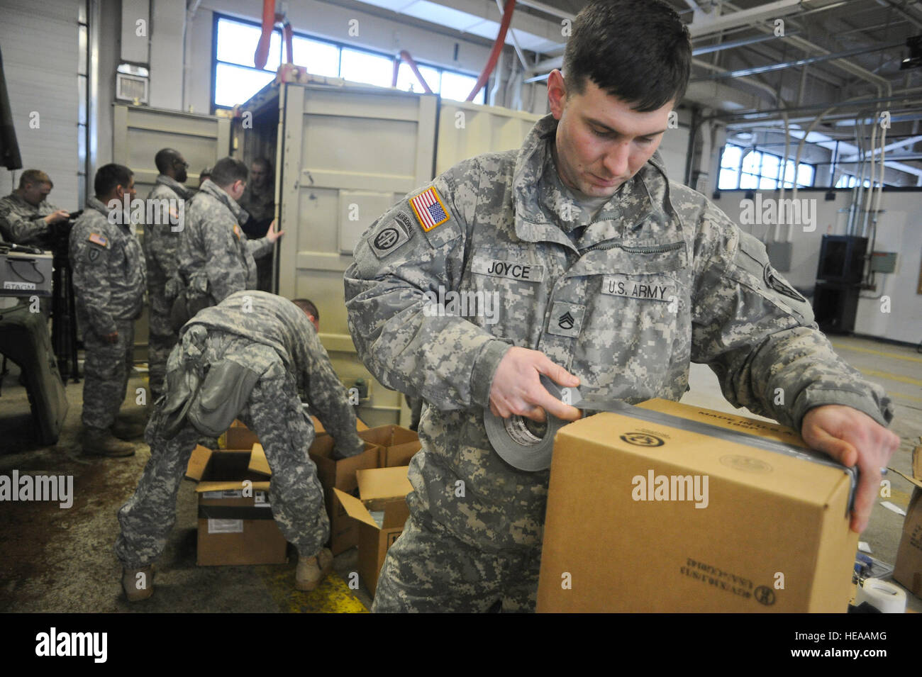 Army Staff Sgt. Barry Joyce, a native of Martinsville, Va., tapes a box to load batteries in as fellow soldiers Stock Photo