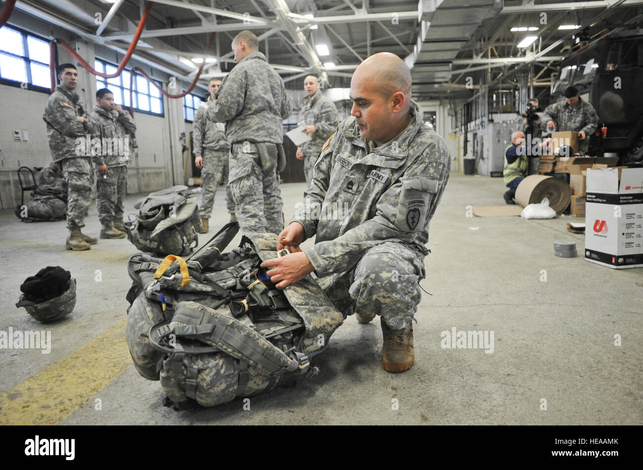Army Sgt. 1st Class Randall Summerford, a native of Oxnard, Calif., rigs his rucksack for a parachute jump as fellow Stock Photo