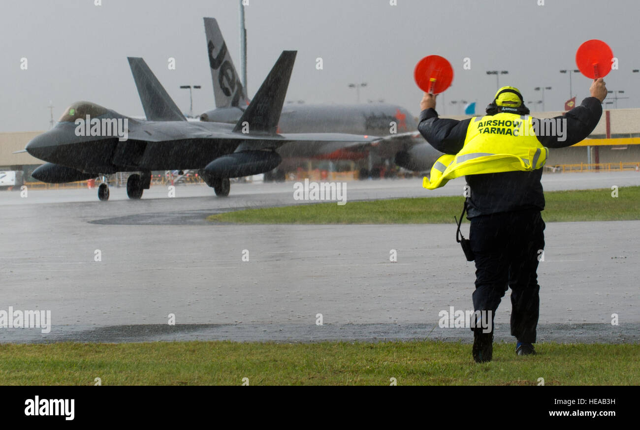 Lyn Jones, Aircraft Ground Operation Aviation Services section leader blue, marshalls an F-22 Raptor assigned to - Stock Image