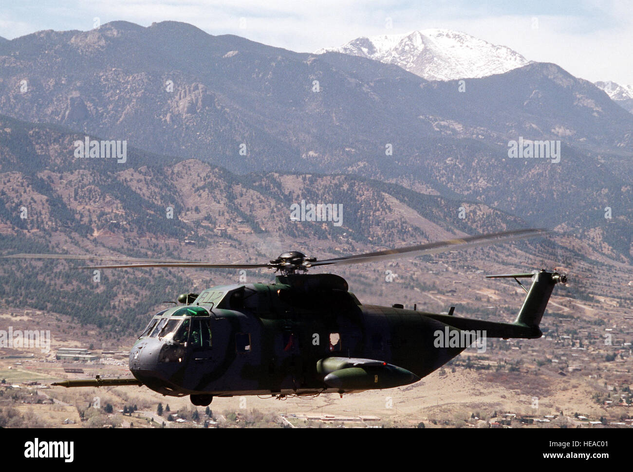 A 71st Air Rescue Squadron (71st ARS) HH-3E Jolly Green Giant helicopter flies near Pike's Peak en route to - Stock Image