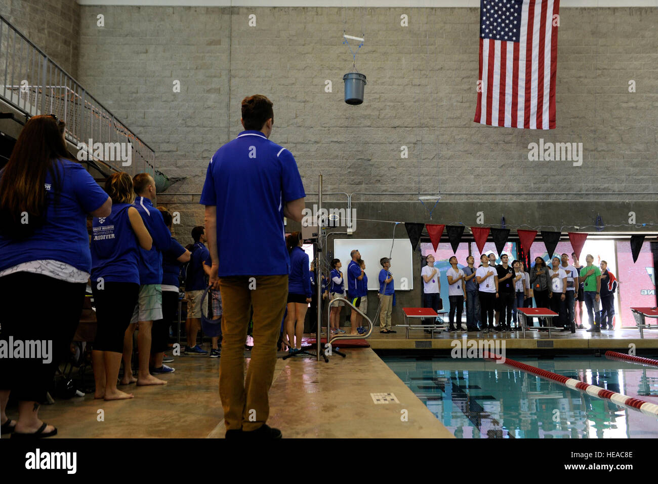 Air Force Trials swimming competitors, staff and volunteers, stand for the singing of the national anthem during - Stock Image
