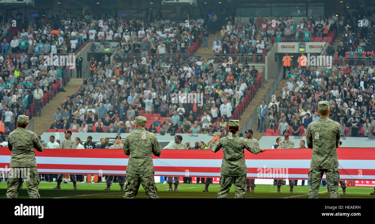Airmen from Royal Air Force Lakenheath, England, hold the U.S. flag before the Miami Dolphins – Oakland Raiders - Stock Image