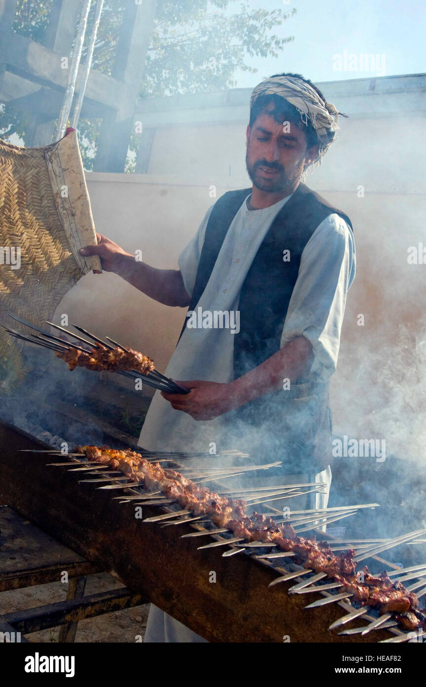 A local cook grills kabobs in preparation for a feast for members of the Kapisa Provincial Reconstruction Team, - Stock Image