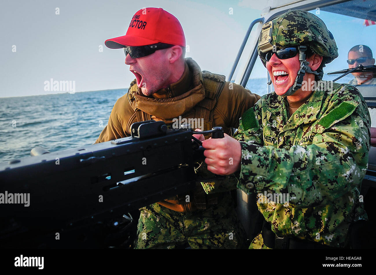 Petty Officer 1st Class Nicholas Sturges (left), gunner's mate, and Petty Officer 3rd Class Amanda Herr (right), Stock Photo
