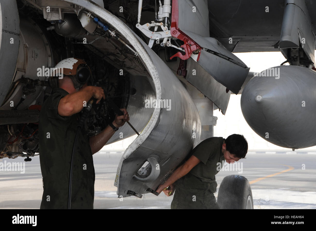Cpl. Kristine Anderson (right) holds the engine bay door open on an EA-6B Prowler while Cpl. Shelby Coville uses a high-pressure water spray during a 14-day aircraft wash in Southwest Asia, September 25, 2012. The 14-day aircraft wash removes dirt and build-up residue that can damage the aircraft. Anderson is assigned to the Marine Tactical Electronic Warfare Squadron Two and Coville is assigned to the Marine Tactical Electronic Warfare Squadron Three. Both are deployed from the Marine Corps Air Station Cherry Point, N.C. Staff Sgt. Sheila deVera) Stock Photo