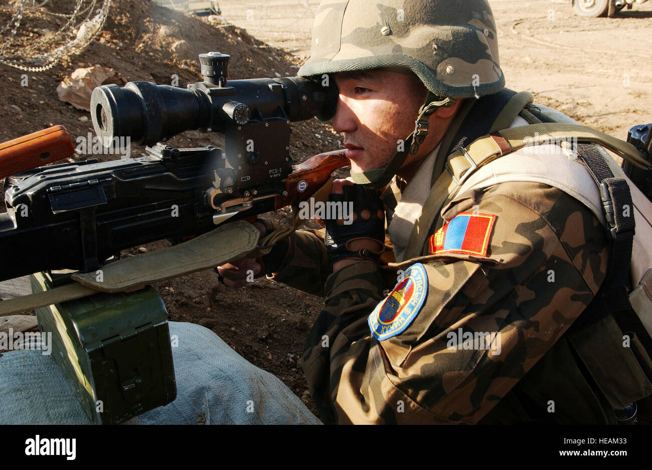 A Mongolian Quick Reactionary Force (QRF) Army Soldier scans the area with his AKMS 7.62 Rifle utilizing a bunker - Stock Image