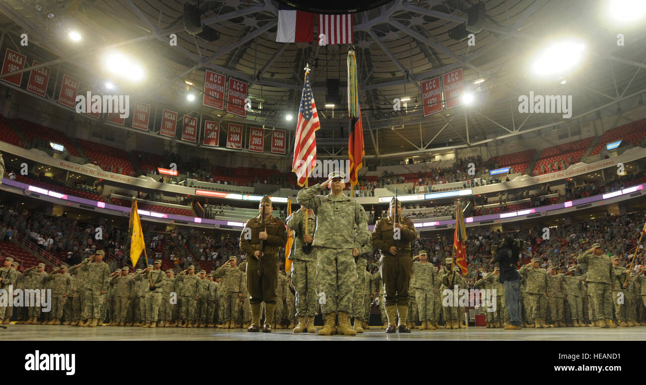 U.S. Soldiers salute during the playing of the national anthem during a homecoming ceremony at the RBC Center in - Stock Image