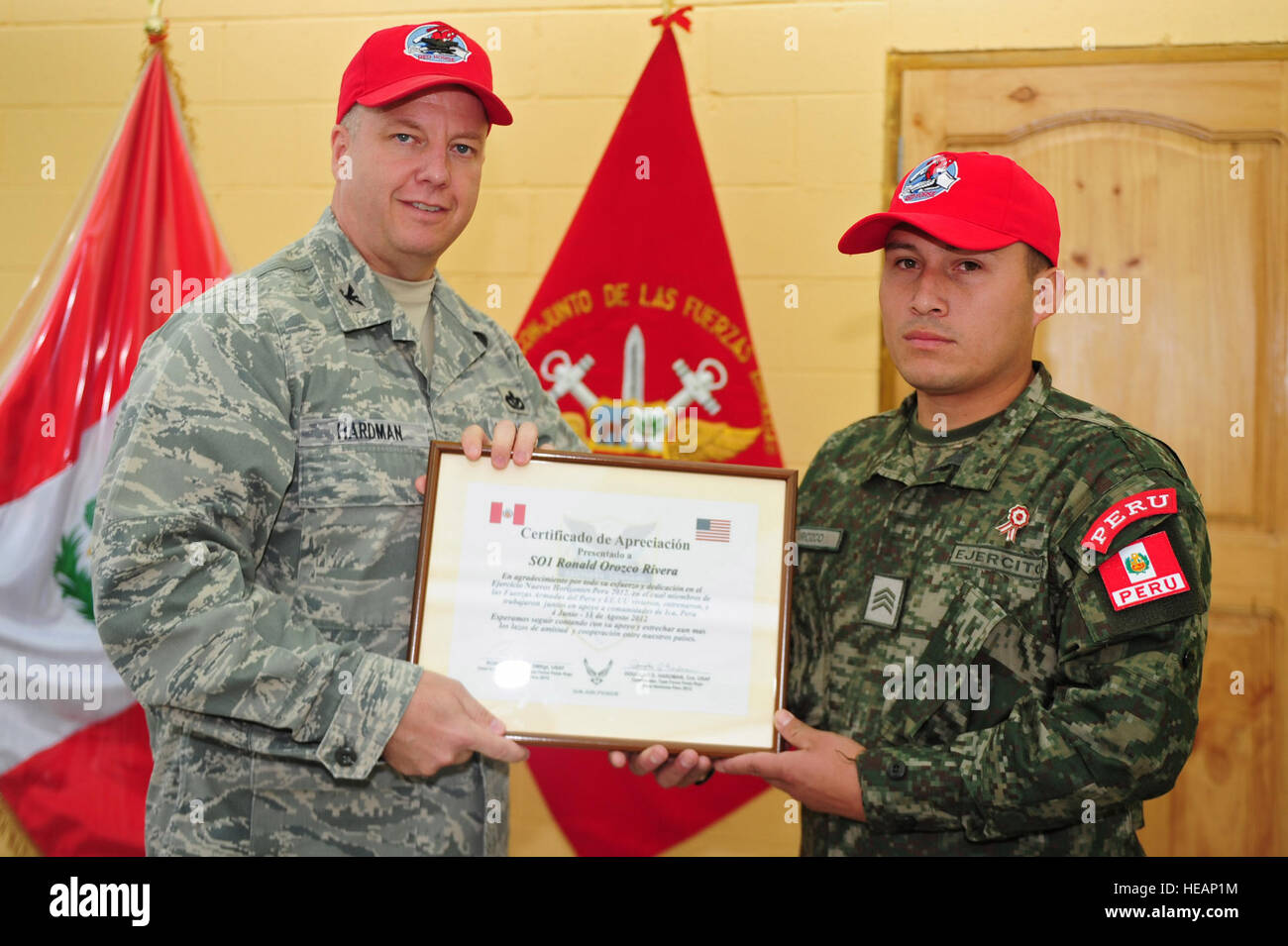 U.S. Air Force Col. Douglas Hardman presents a Red  Horse hat and Certificate to a Peruvian soldiers who contributed - Stock Image