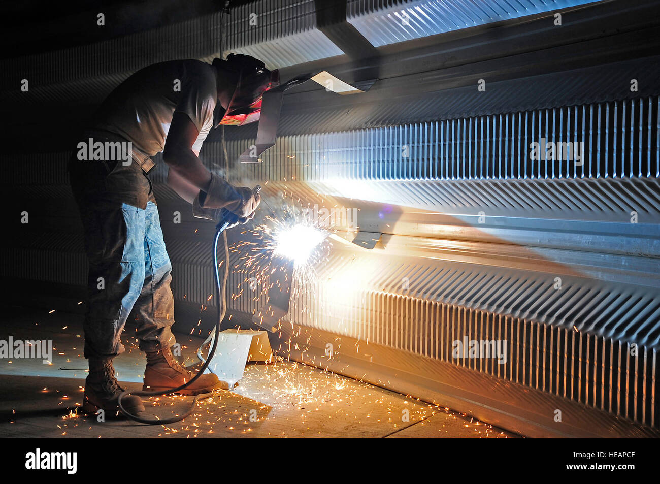 U.S. Air Force Airman 1st Class Robert Campbell Jr., 557th Expeditionary RED HORSE Squadron, uses a welder to modify - Stock Image