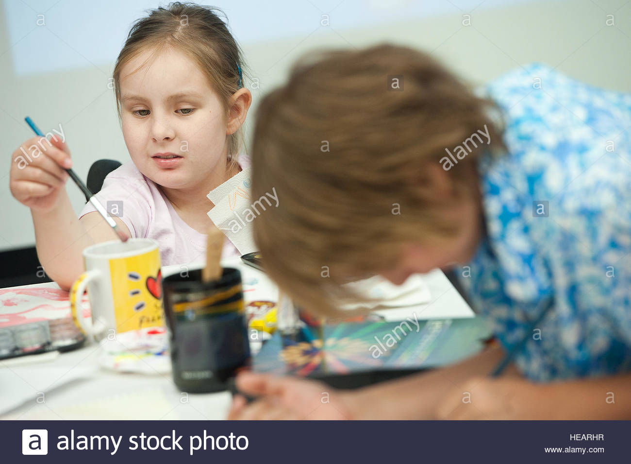 Haley Tyrrell, 10, paints with her brother, Zachary Tyrrell, 8, during the eighth annual Oncology on Canvas event - Stock Image