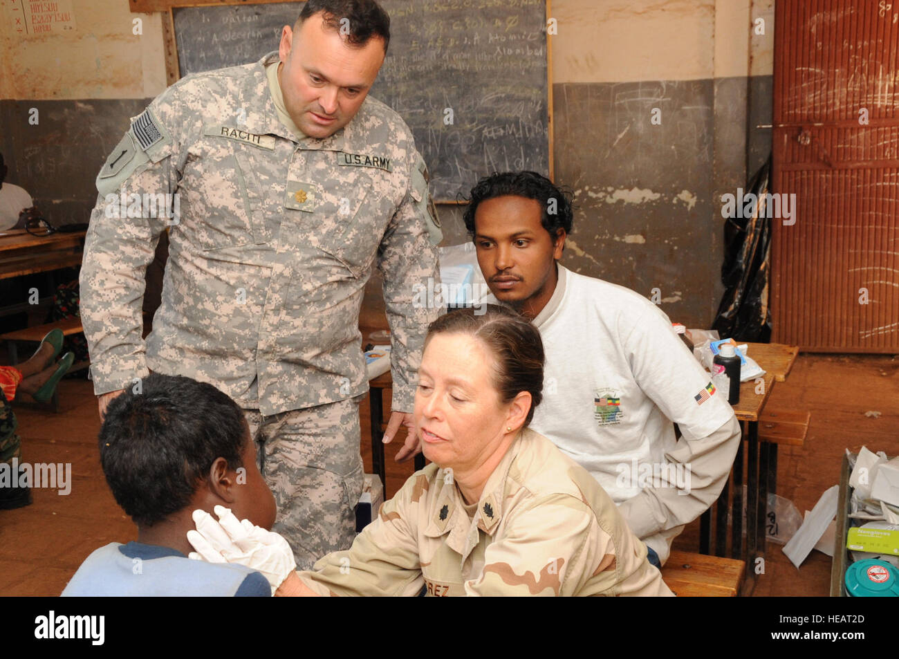 US Army MAJ Marc Raciti and a local medical provider watch as Navy CMDR Nora Perez examines a young boy during a - Stock Image