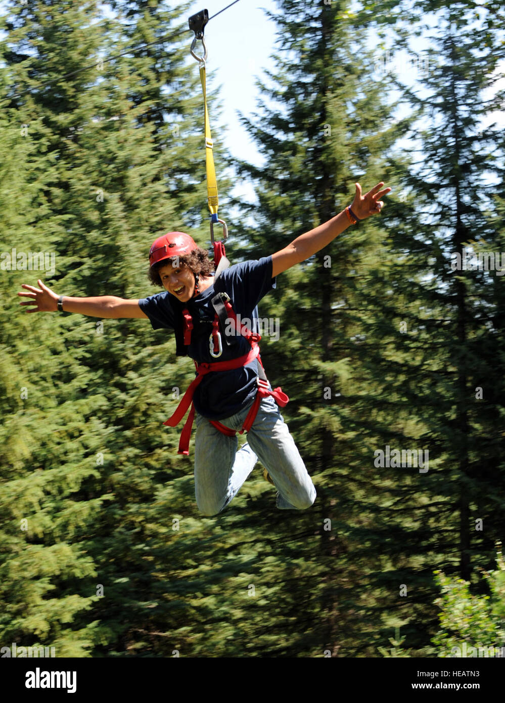MOUNTAIN HOME AIR FORCE BASE, Idaho -- Sterling Adamson, camp participant, swings down a high-ropes zip line Aug. - Stock Image