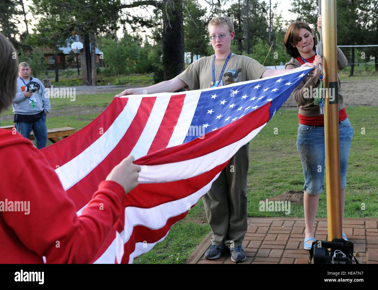 MOUNTAIN HOME AIR FORCE BASE, Idaho -- Brandon Owens, camp participant, presents the flag at table top before folding - Stock Image