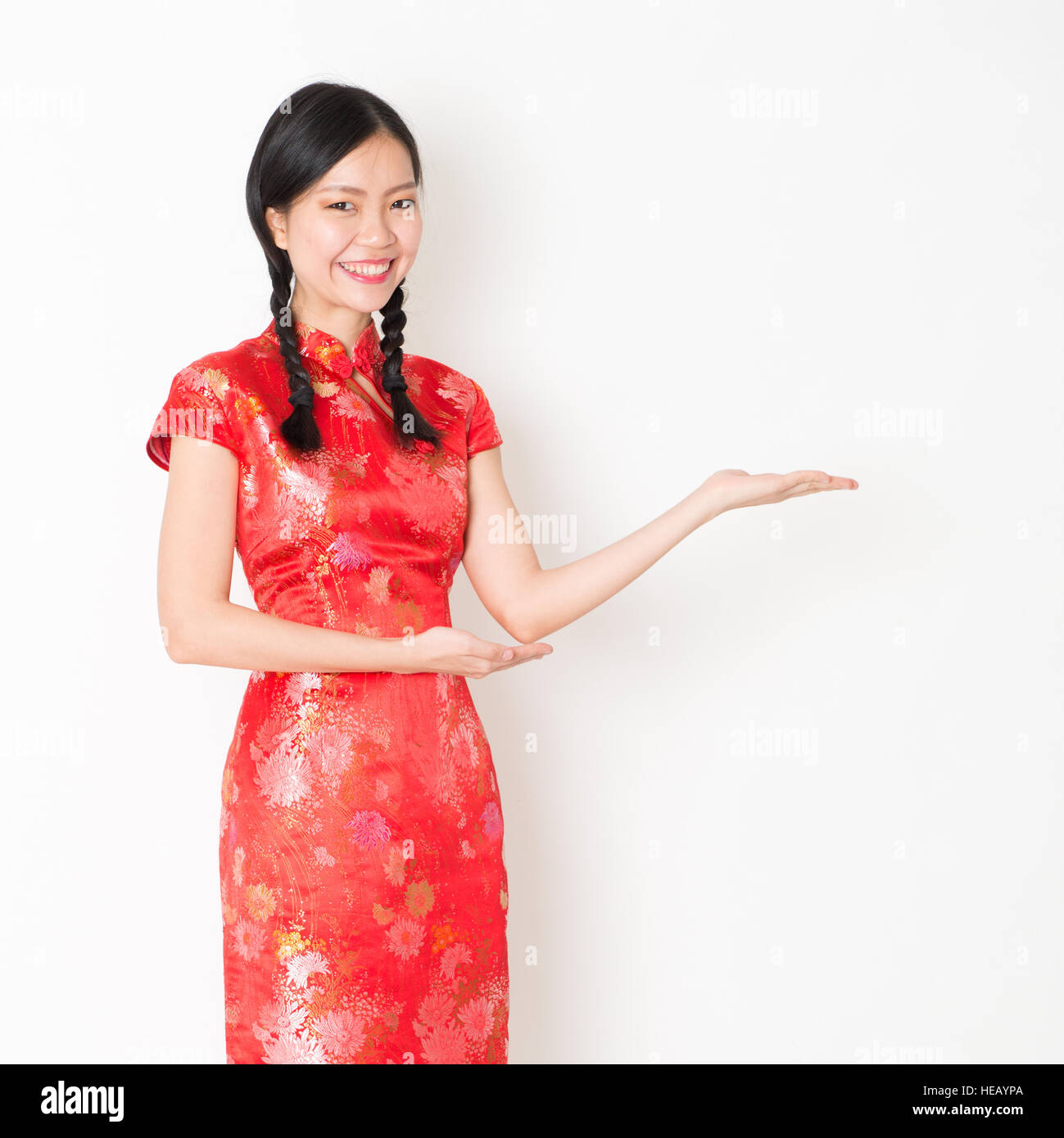 7b1f4151e Portrait of young Asian woman in traditional qipao dress smiling and hand  showing something, celebrating Chinese Lunar New Year or spring festival, st