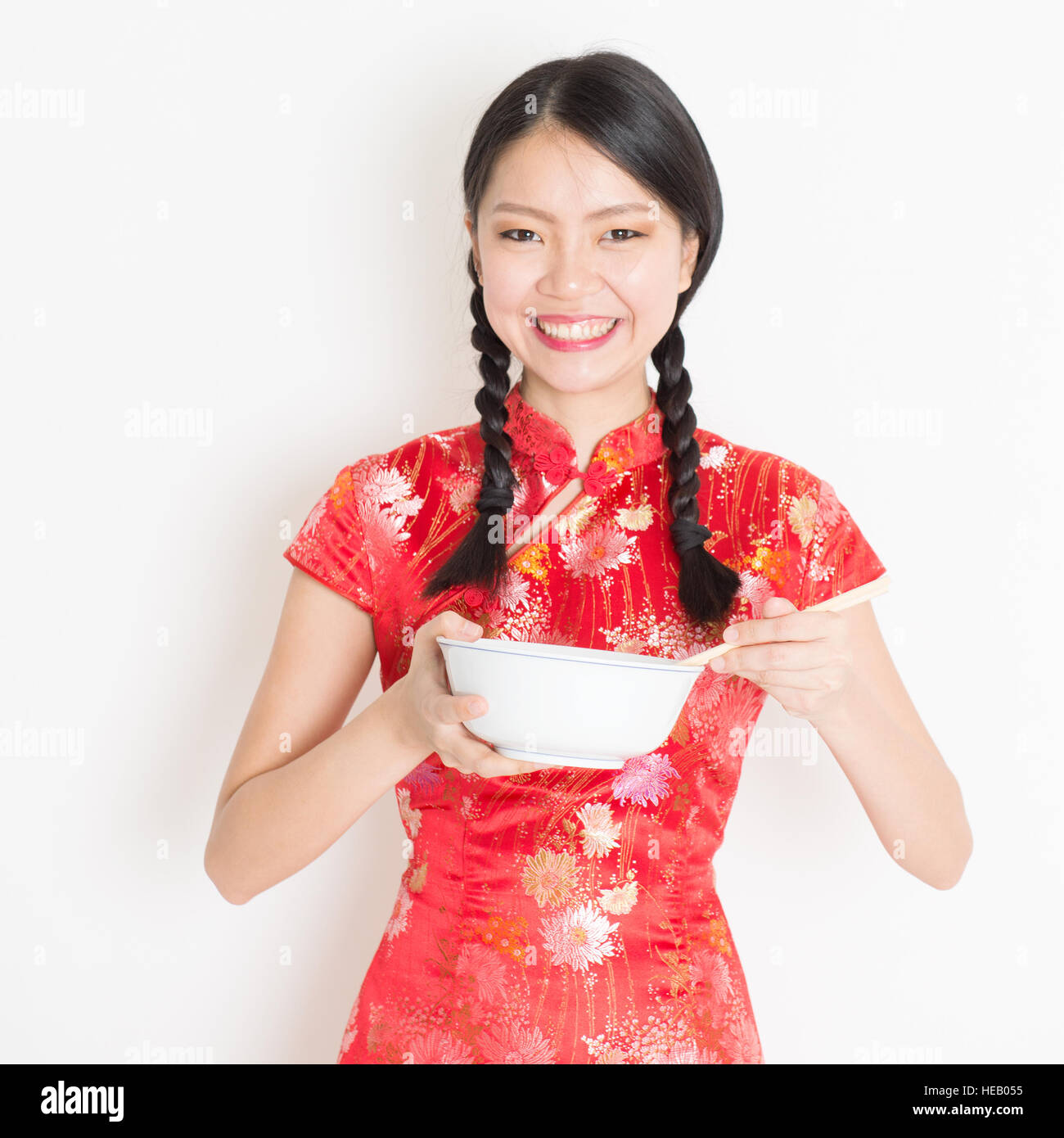 cb4c5e4c0 Portrait of young Asian girl in traditional qipao dress eating, hand  holding bowl and chopsticks, celebrating Chinese Lunar New Year or spring  festiva