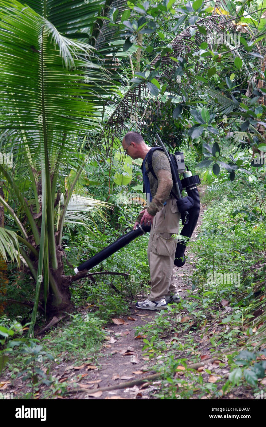 Col. James Swaby uses a powered aspirator to collect mosquitoes in a northern Thailand jungle in August 2007. The - Stock Image