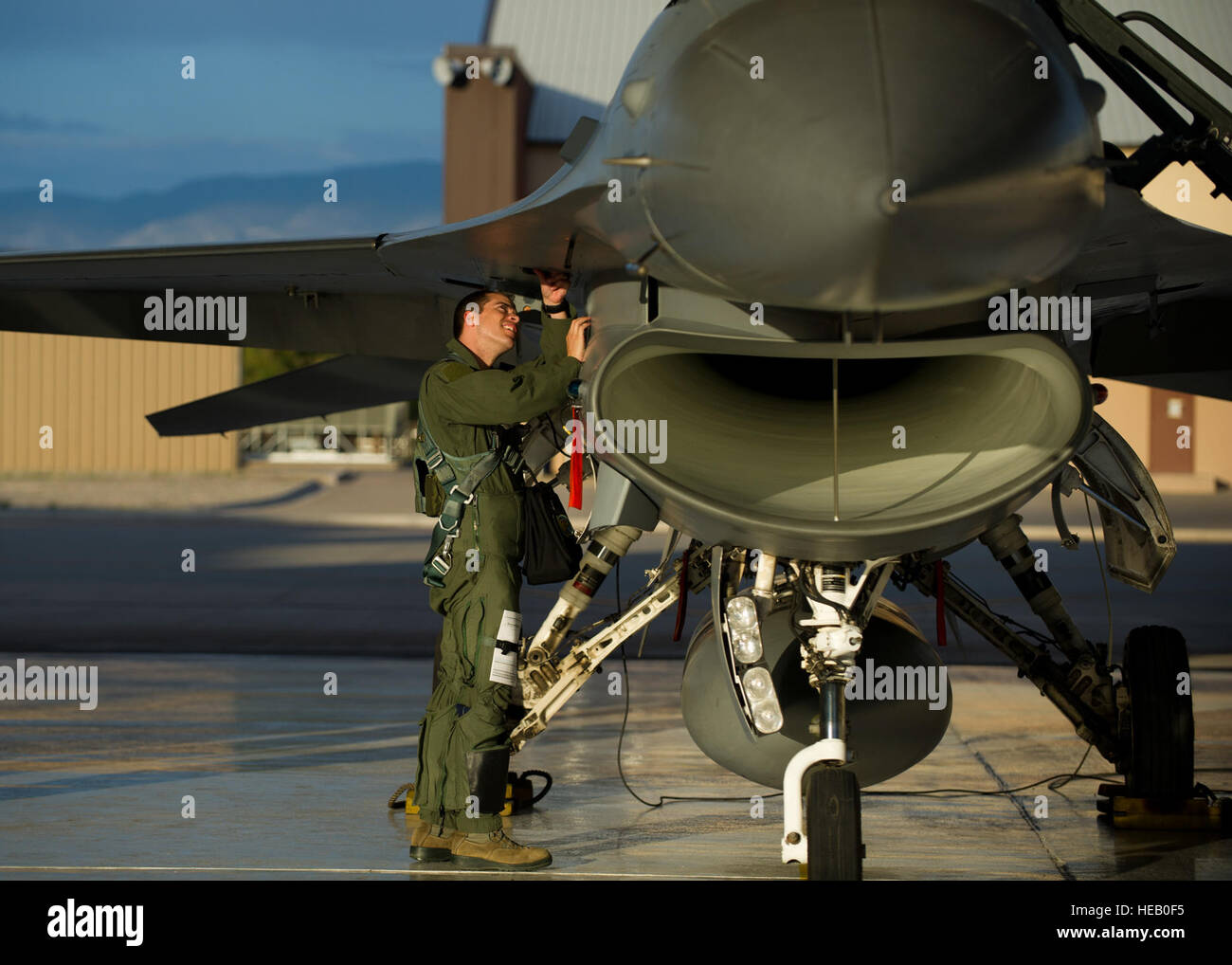 Captain Jake Pippenger, 54th Fighter Group pilot, inspects an F-16 Fighting Falcon to prepare for a training sortie - Stock Image