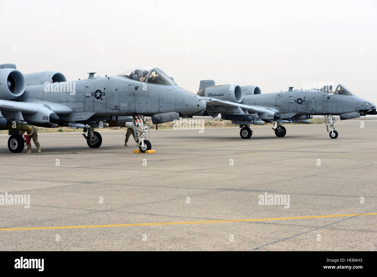 Two A-10 Thunderbolt IIs from the 163rd Expeditionary Fighter Squadron go through de-arming procedures following Stock Photo