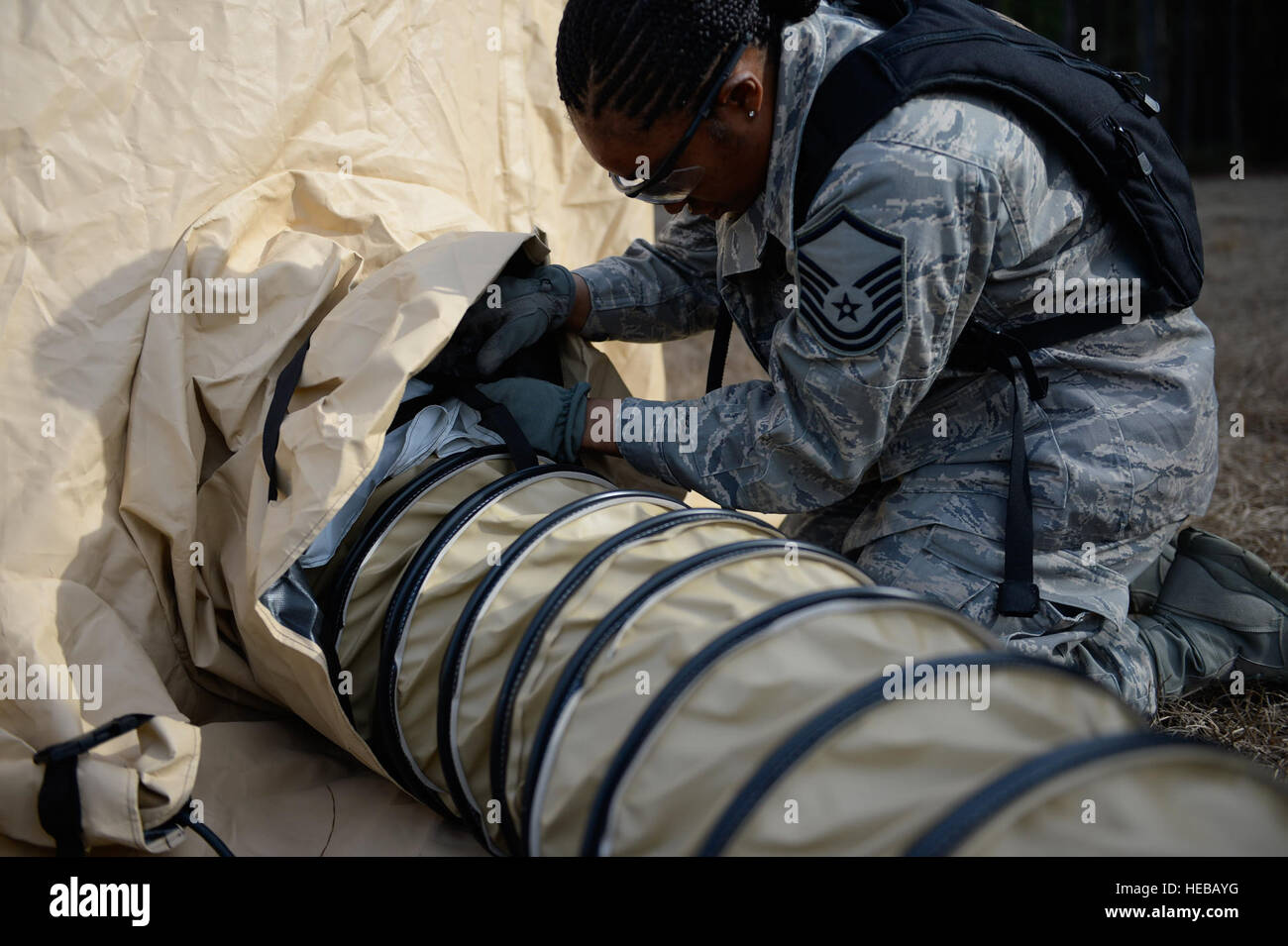 U.S. Air Force Master Sgt. Luella DeLee, with the 1st Combat Camera Squadron, positions a heating vent inside a - Stock Image