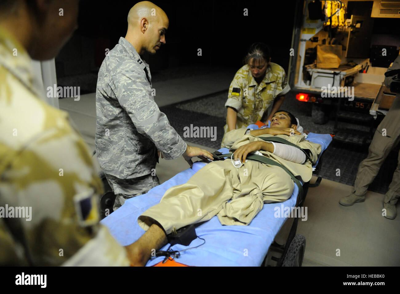 U.S. Air Force Capt. Jac Solghan, Aeromedical Evacuation Liaison Team flight clinical coordinator, comforts an Afghan - Stock Image