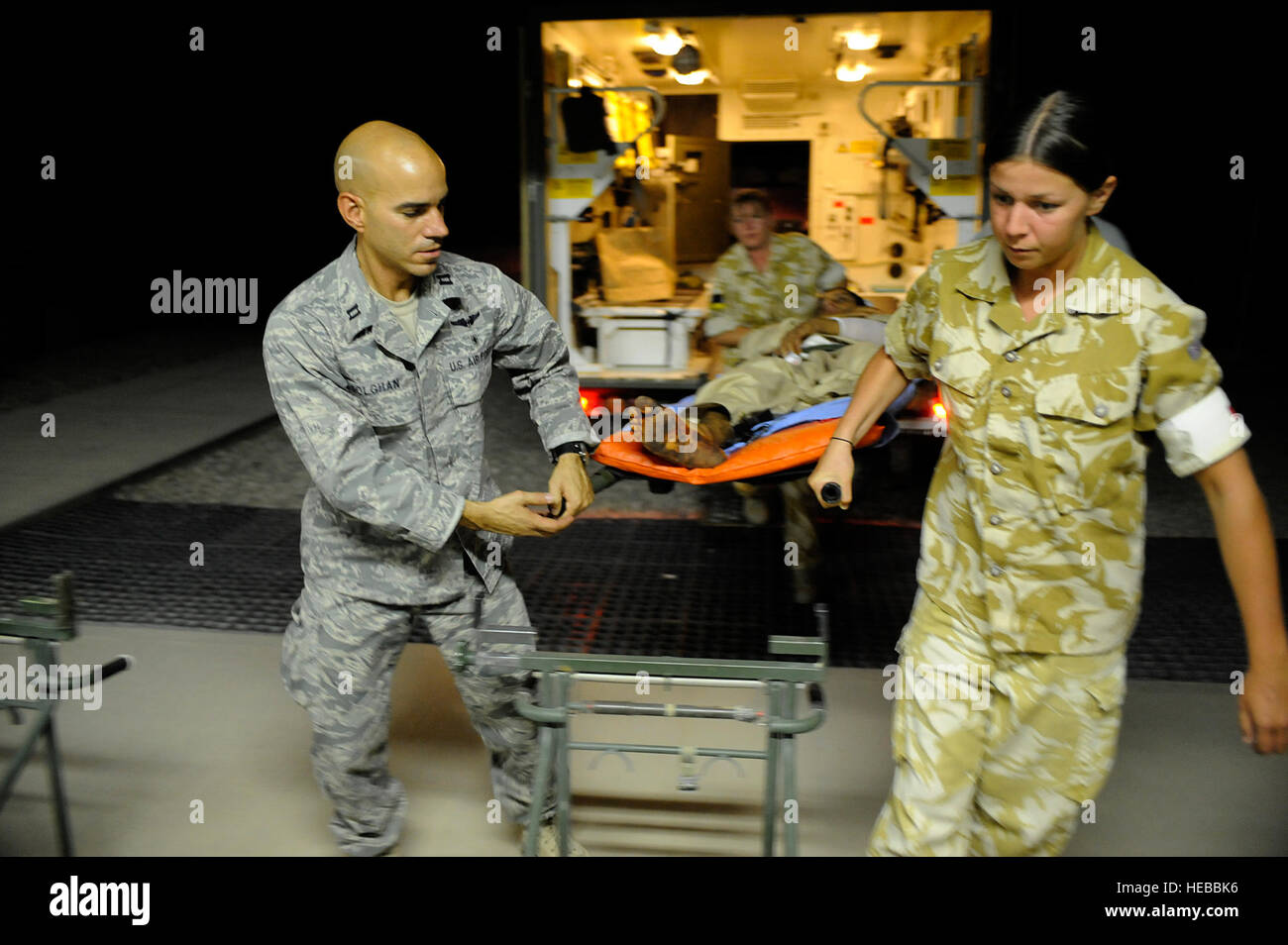 U.S. Air Force Capt. Jac Solghan, Aeromedical Evacuation Liaison Team flight clinical coordinator, and British soldiers - Stock Image