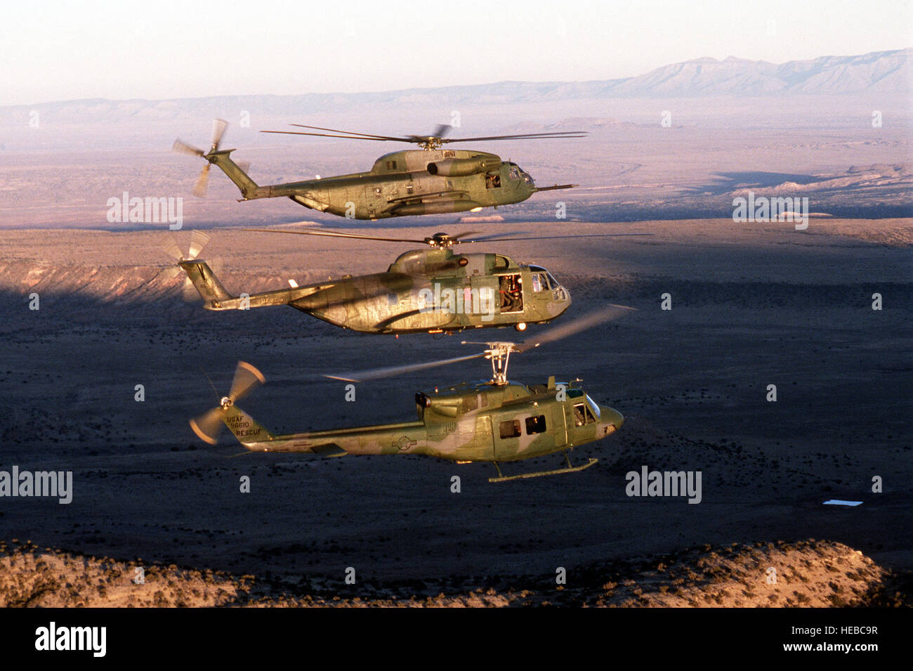 An HH-53 Super Jolly, an H-3 Jolly Green Giant and a UH-1 Iroquois helicopter fly in formation near the 531st Field - Stock Image