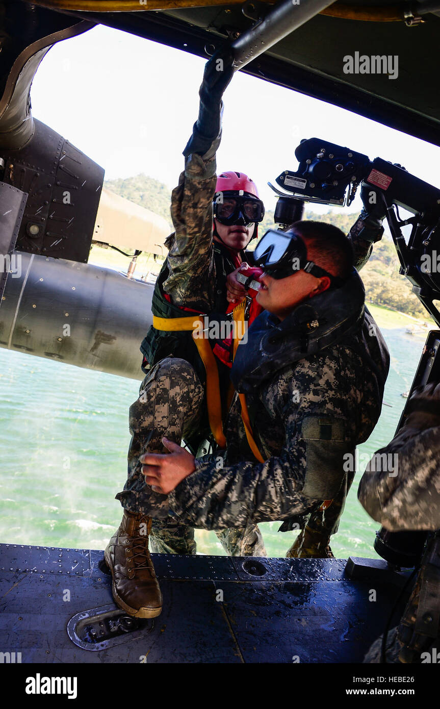 A medic from the 1-228th Aviation Regiment climbs in to a UH-60 Black Hawk helicopter after being lowered to retrieve Stock Photo