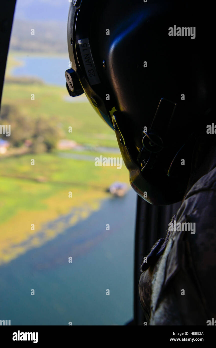 A crew chief assigned to the 1-228th Aviation Regiment looks for the U.S. Army Special Operations members in Lake Stock Photo