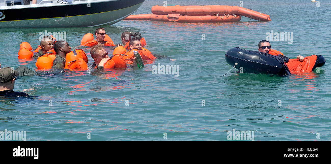 A water survival training course student climbs onto a one-man life raft while the rest of the class observes at - Stock Image