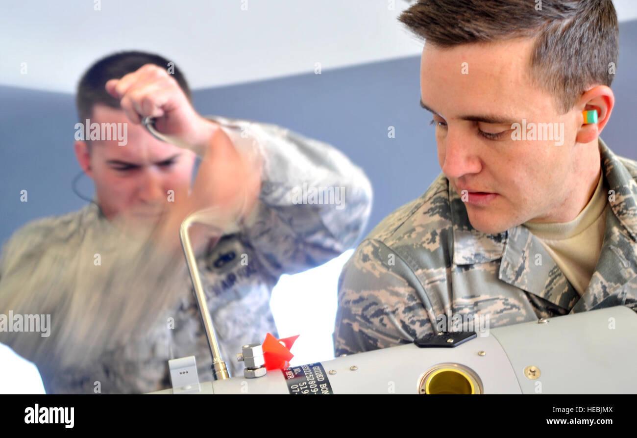 Senior Airman Jeffrey Salyer, 432nd Aircraft Maintenance Squadron weapons load crew member, helps Staff Sgt. Jason - Stock Image
