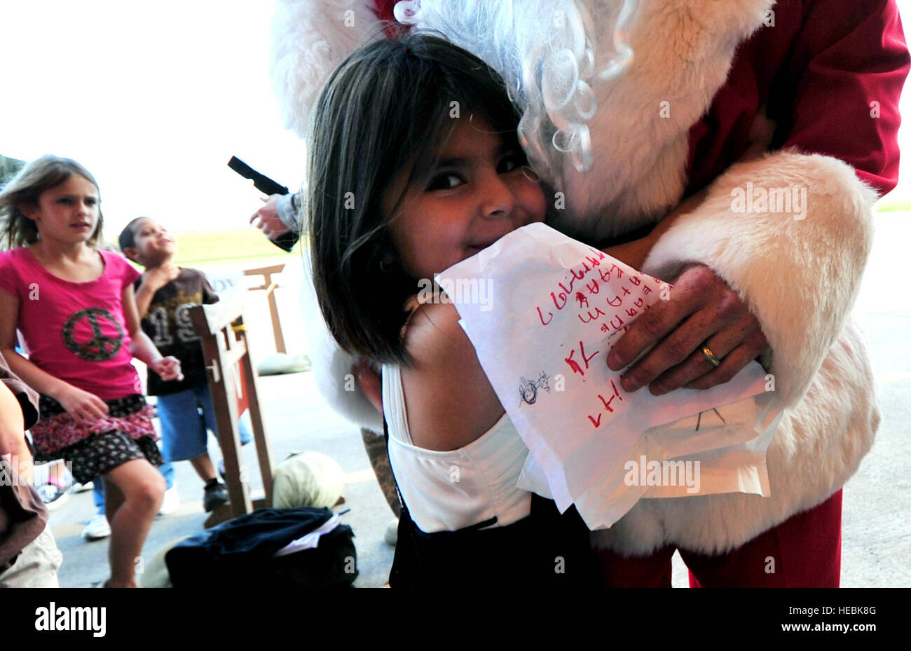 Santa Claus hugs children attending a holiday homecoming party at the 33rd Rescue Squadron maintenance hangar Dec. - Stock Image