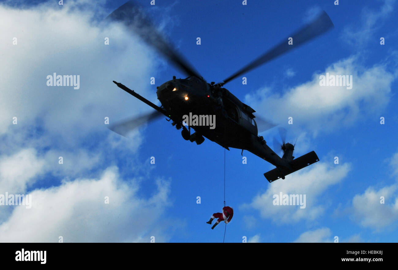 Santa Claus fast drops from a 33rd Rescue Squadron Pave Hawk before handing out presents to children attending a - Stock Image