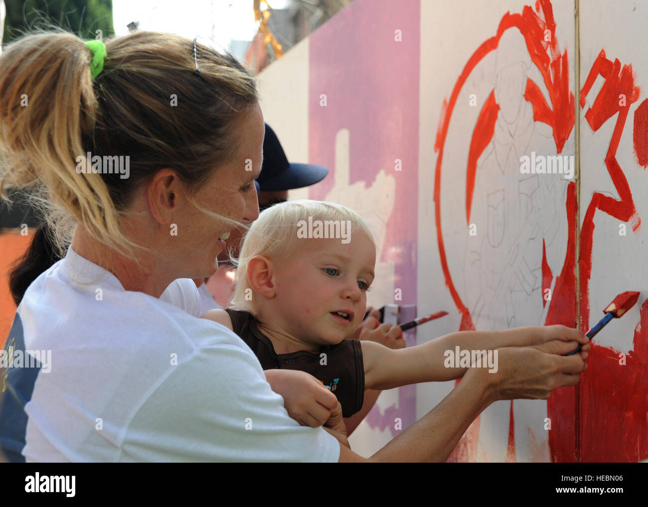 Linne Gherdovich and son Hudson, paint a mural of a Turkish soldier at the Kazim Karabekir School for Autism, June 9, 2014, Adana, Turkey. Gherdovich is a coordinator with the organization Love Impact Give Help Teach Serve, or LIGHTS located at Incirlik Air Base, Turkey. The group of active duty members, civilians and dependents of all ages focuses on helping the community with simple art projects at special needs schools around Adana. (U.S. Air Force photo by Staff Sgt. Veronica Pierce/Released) Stock Photo