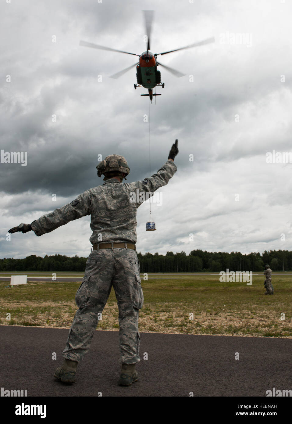 Staff Sgt. Timothy Kennedy marshals a Latvian Mi-8 helicopter in part of sling-load operations training during the - Stock Image