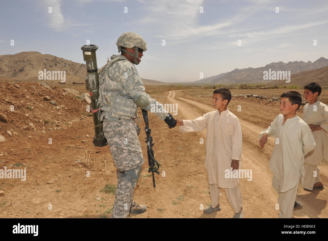 Pfc. Jessie Bell, Ghazni Provincial Reconstruction Team security forces member, shakes hands with an Afghan boy, Stock Photo