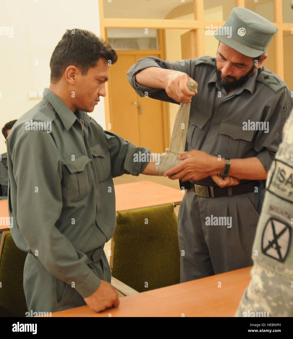 Afghan National Police Maj. Aminullah practices wrapping an emergency trauma bandages on ANP Sgt. Jaleel during - Stock Image