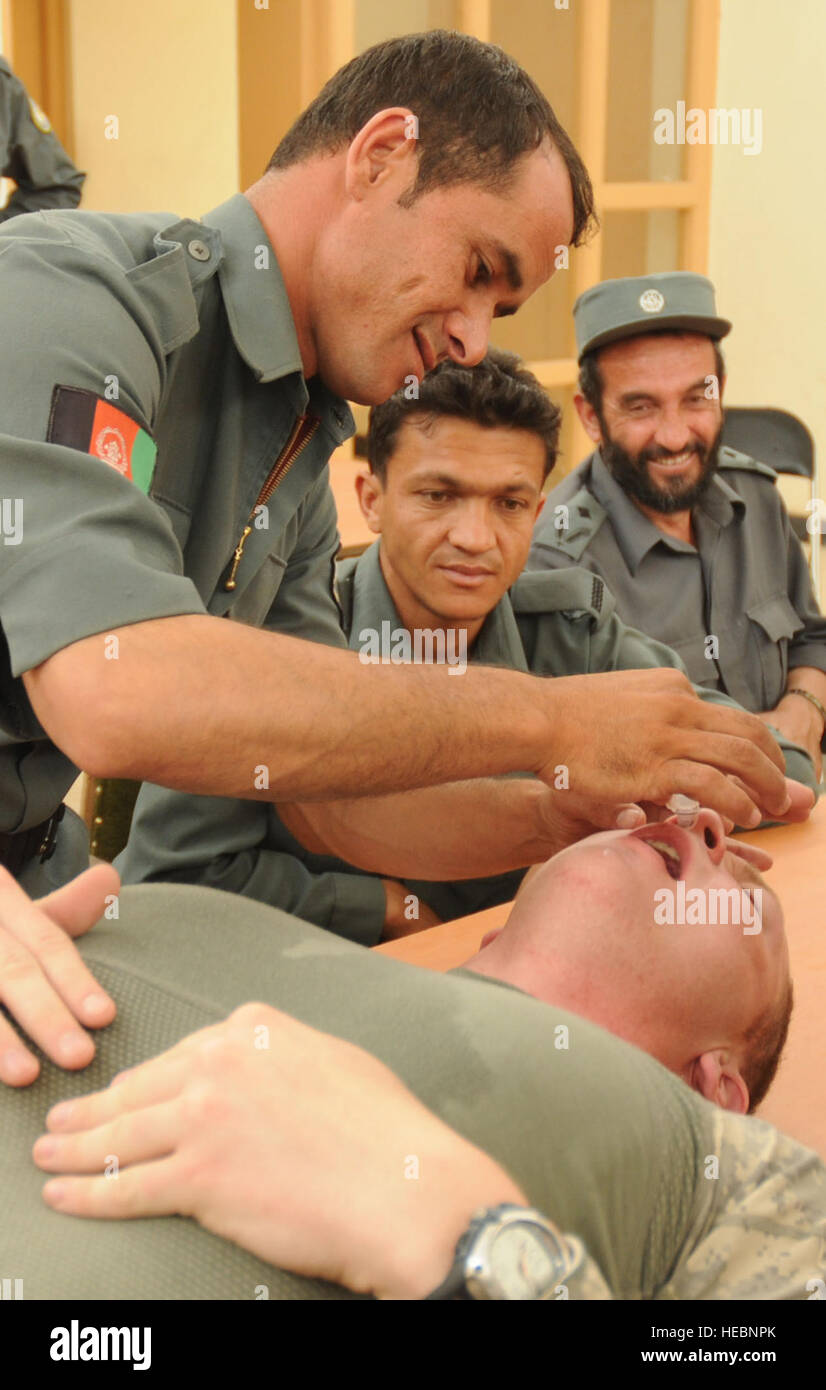 Afghan National Police Sgt. Hameed inserts a nasopharyngeal airway tube into the nose of 1st Lt. Michael Kehoe, - Stock Image